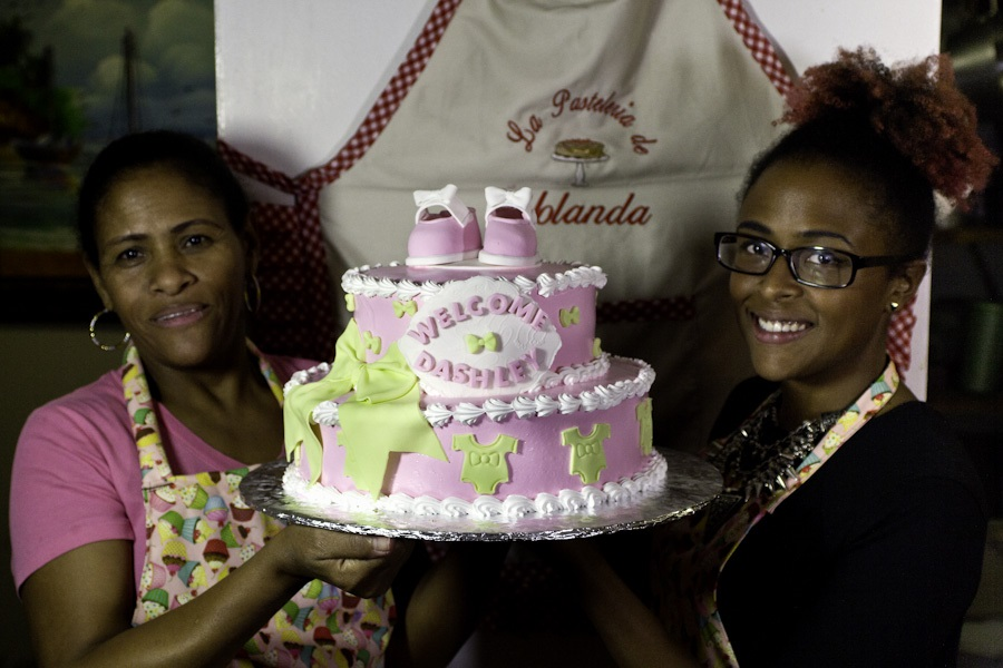 Yolanda Andujar (R) and Astrid Andujar (L), holding up a Dominican cake they made together in their Bronx apartment bakery. (Photo: Néstor Pérez-Molière)